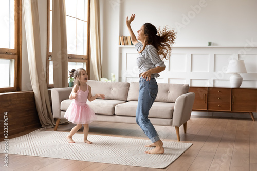 Obraz Crazy energetic family of two dancing in living room. - fototapety do salonu