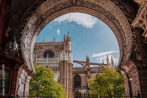 Beauty of Seville Cathedral. View to cathedral North facade and Oranges yard through the arch gate. Largest Gothic church in the world. Cathedral of Saint Mary of the See, Andalusia, Spain, Europe