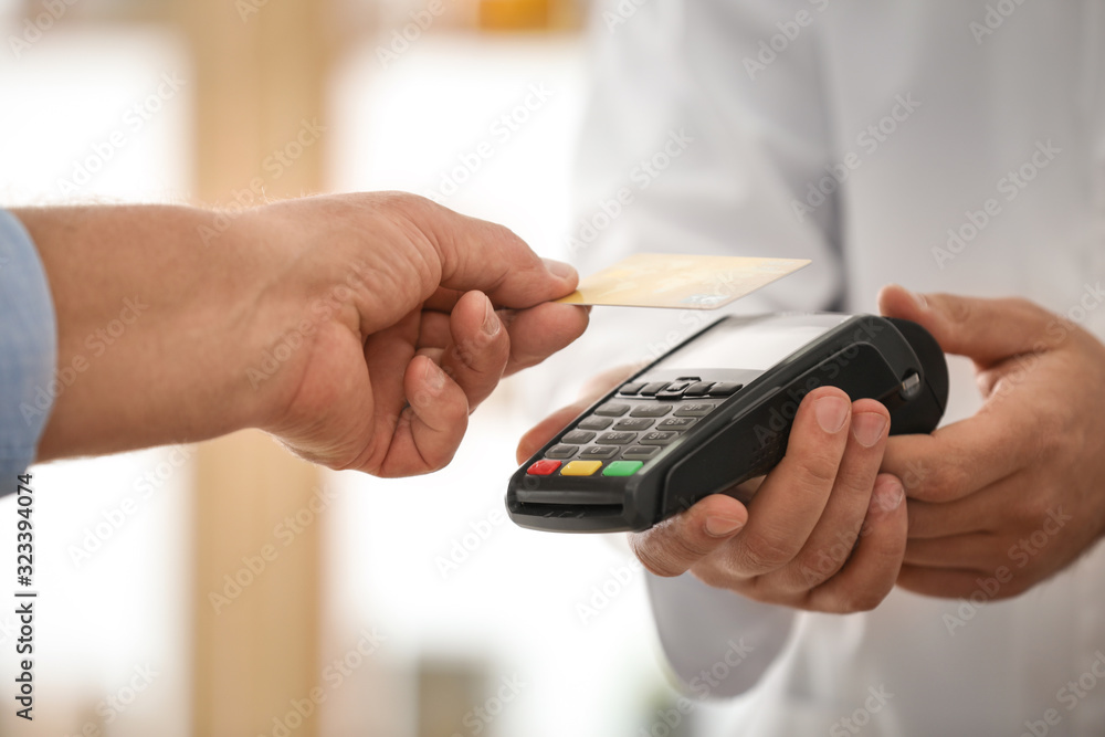 Fototapeta Customer using terminal for contactless payment with credit card in pharmacy, closeup