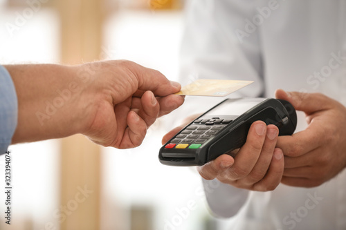 Customer using terminal for contactless payment with credit card in pharmacy, cl Fototapeta
