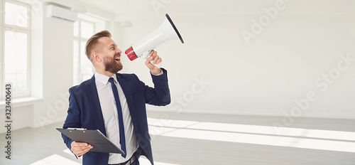 Fotografía Male real estate agent shioting in megaphone smiling in white real estate room a