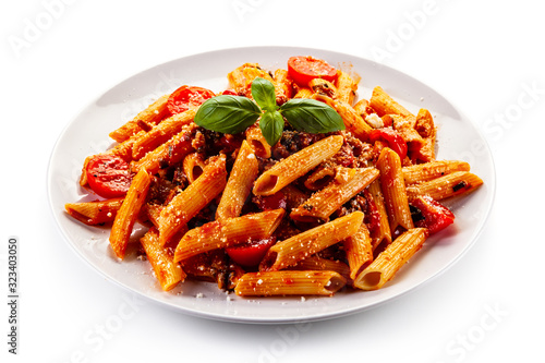 Penne with meat, tomato sauce and vegetables on white background Fototapet