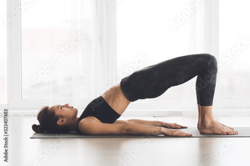 Obraz Relaxed girl streching body in bridge pose - fototapety do salonu