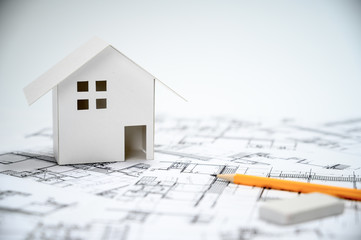 Construction industry concept with pencils and house models on architectural drawings.