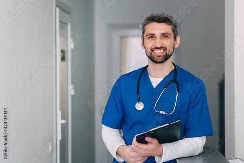 Obraz male nurse with stethoscope standing at clinic. He is smiling and looking at the camera. - fototapety do salonu