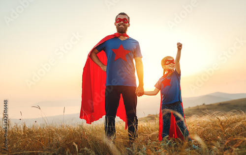 Fototapeta concept of father's day. dad and child daughter in hero superhero costume at sunset  . obraz