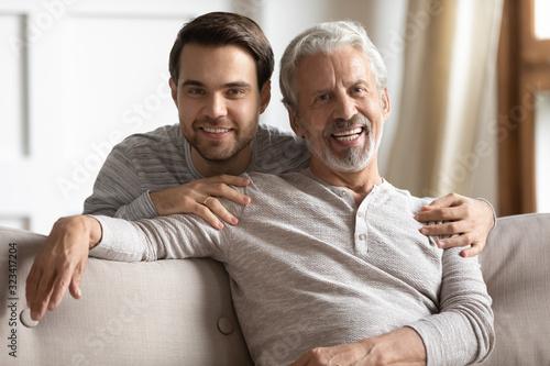 Fotografía Head shot portrait young man embracing sitting on couch dad.