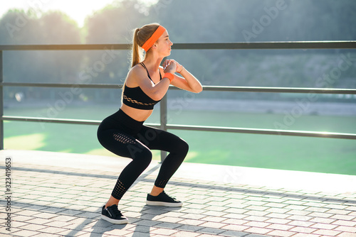 Canvas-taulu Gorgeous sporty girl in black sportswear and orange headband which squating during fitness training at stadium outdoors
