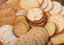Various Organic Crispy Wheat, Rye And Corn Flatbread Crackers With Sesame And Salt In Round Plate On Wooden Background. Top View