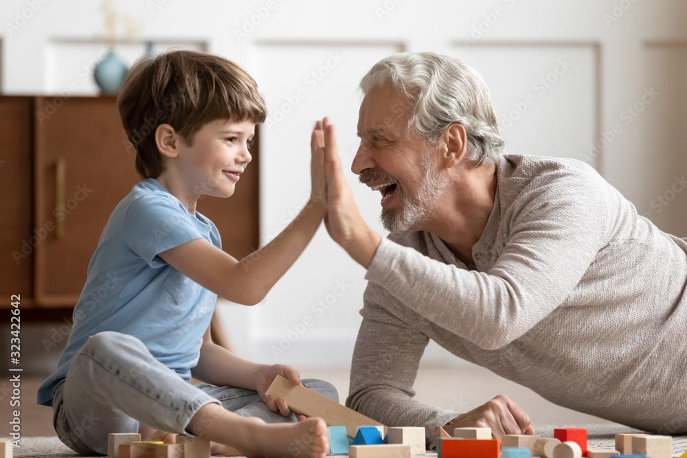 Fototapeta Funny little boy giving high five to joyful older grandfather.