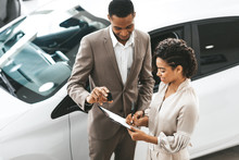 Lady Buying Car Signing Papers With Dealer In Dealership Store