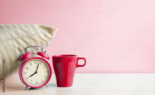Photo Morning Red Alarm clock and red mug near the pillow on the bedside table on pink