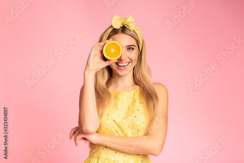 Fototapeta Blonde girl holding orange slice next to eye obraz