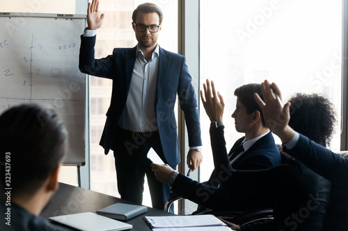 Confident businessman mentor raising hand with colleague question in boardroom Canvas Print