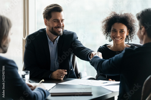 Fototapeta Happy successful businessman in suit shaking hand of business partner