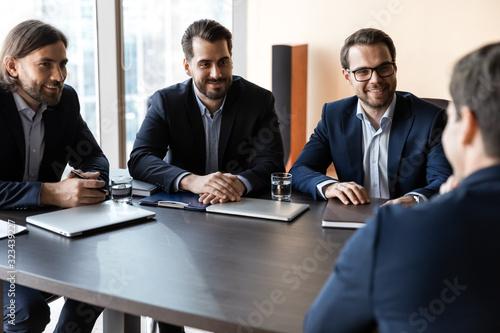 Fototapeta Applicant sitting in front three happy HR businessmen speaking. obraz na płótnie
