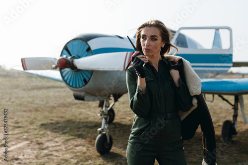 Fotografie, Obraz girl in green overalls with one hand holds a walkie-talkie with the other holds