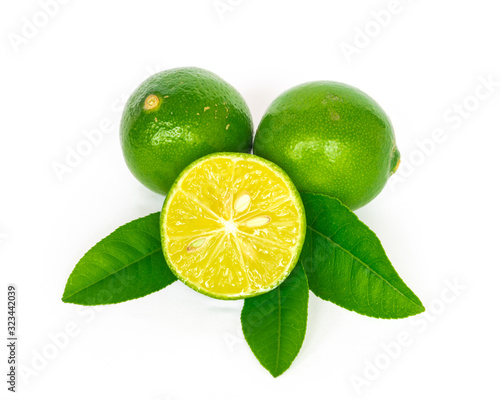 Two homegrown raw Asian limes with half cut slices and green leaves isolated on Canvas Print
