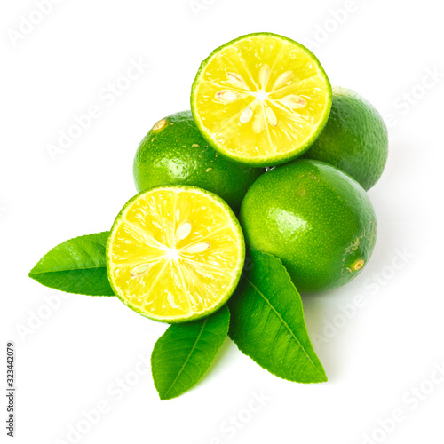 Pile of homegrown Asian limes with half cuts slices and green leaves isolated on Canvas Print