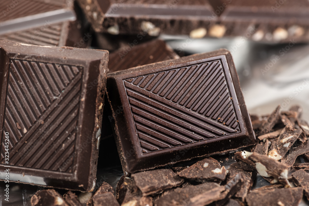 Fototapeta Chocolate bar pats pieces background with almond nut