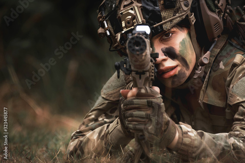 Fotomural close up of woman soldier holding gun laying on the ground