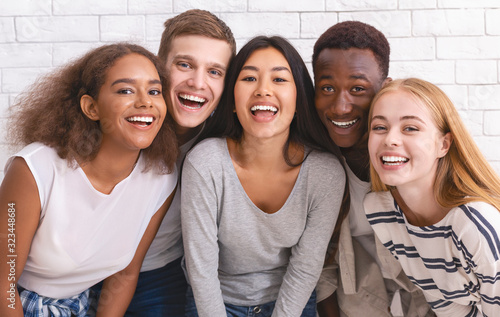 Portrait of happy multiethnic young friends over white wall background