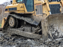 Dirty Bulldozer Standing In The Mud. Autumn Construction Site With Working Machines.