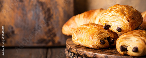 Valokuvatapetti Freshly baked sweet buns puff pastry with chocolate and croissants on old wooden background