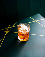 Whiskey With Ice In A Crystal Glass On A Green Background With Golden Stripes