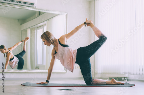Young woman doing stretching exercise by mirror in bright yoga class room Wallpaper Mural