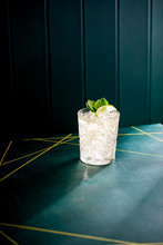 Drink With Fresh Mint Leaves, With Lime In A Crystal Glass On A Green Background With Golden Stripes