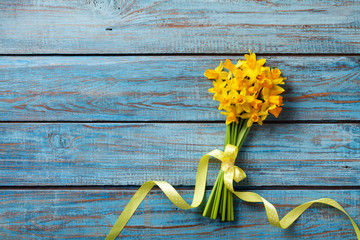 Spring daffodil flowers on blue rustic background. Beautiful bouquet for Women day, Mother day. Top view.