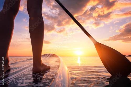 Obraz Stand up paddle boarding or standup paddleboarding on quiet sea at sunset with beautiful colors during warm summer beach vacation holiday, active woman, close-up of water surface, legs and board - fototapety do salonu