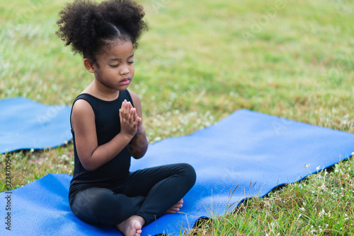 African american little girl sitting on the roll mat practicing meditate yoga in Canvas Print