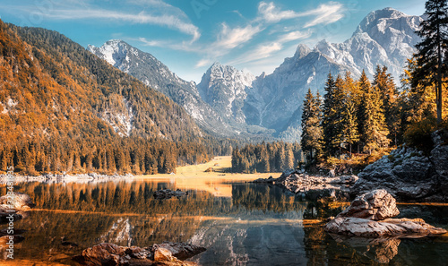 Wall mural - Awesome sunny landscape in the forest. Wonderful Autumn scenery. Picturesque view of nature wild lake. Sun rays through colorful trees. Incredible view on Fusine lakeside. Amazing natural Background