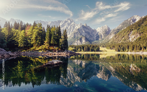 Fototapeta Wonderful Nature landscape. Amazing Mountains lake during sunset. Awesome alpine highlands in sunny day. Picture of wild area. Fusine lake. Italy, Julian Alps. Best travel locations. obraz