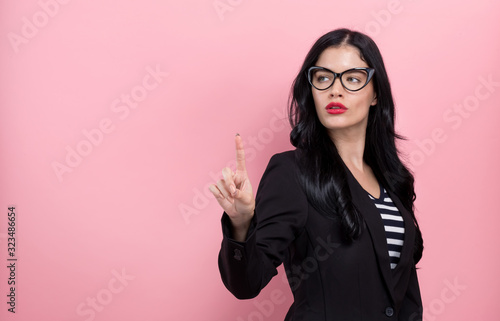 Young woman pointing at something on a pink background