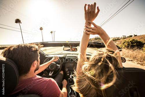 Fototapeta Couple driving on a convertible car obraz