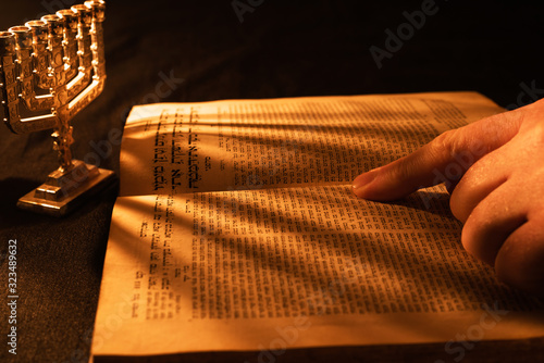 Old Hebrew Bible and silver menorah in light of burning candle on dark background Canvas Print