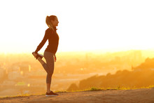 Runner Woman Stretching Leg In City Outskirts At Sunset