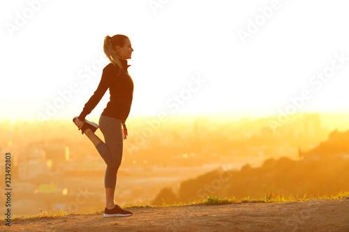 Fototapeta Runner woman stretching leg in city outskirts at sunset obraz