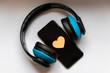 Schwarzes Smartphone mit Herz zum Valentinstag und blauem Funkkopfhörer zeigt Liebe zur Musik und mobilen Musikgenuss dank Musikstreaming und Audiobooks unterwegs immer dabei