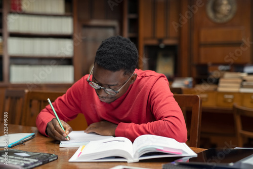 Student in library studying for exam Wallpaper Mural