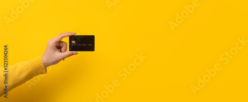 Obraz bank card in hand over yellow background, panoramic mock-up - fototapety do salonu