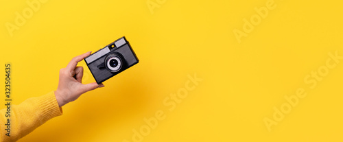 Obraz Woman's hand holds an old film camera on a yellow background, panoramic mock-up with space for text - fototapety do salonu