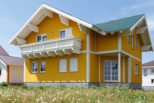 New Yellow House With White Windows And A Large Wooden Balcony Built In The Village.