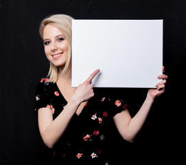 Blonde woman with white board on dark background
