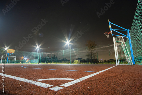 Obraz Outdoors mini football and basketball court with ball gate and basket surrounded with high protective fence brightly illuminated with spotlight lamps at night. - fototapety do salonu