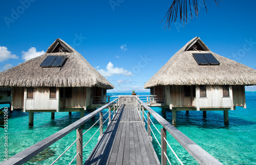 Wooden walkways over the water of the blue tropical sea to authentic traditional Canvas Print