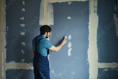 Fototapeta Back view portrait of bearded man working on dry wall while renovating house, copy space obraz